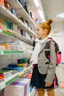 Petite écolière avec sac à dos sur l'étagère en papeterie