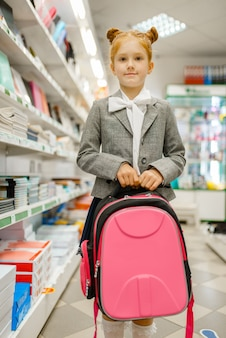 Petite écolière avec sac à dos à la main sur l'étagère de la papeterie