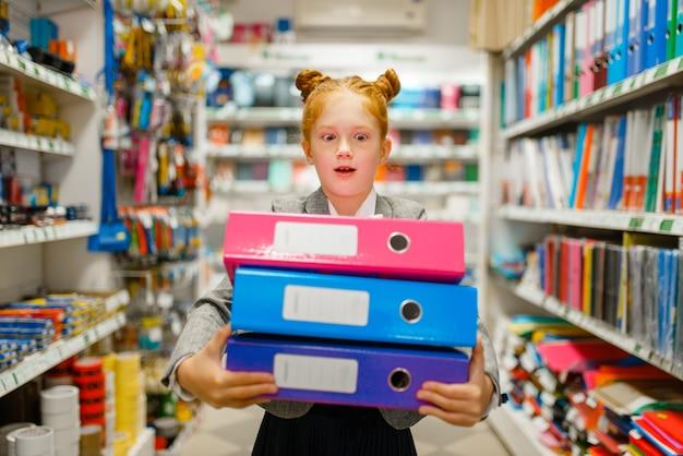 Une petite écolière tient des dossiers colorés dans une papeterie