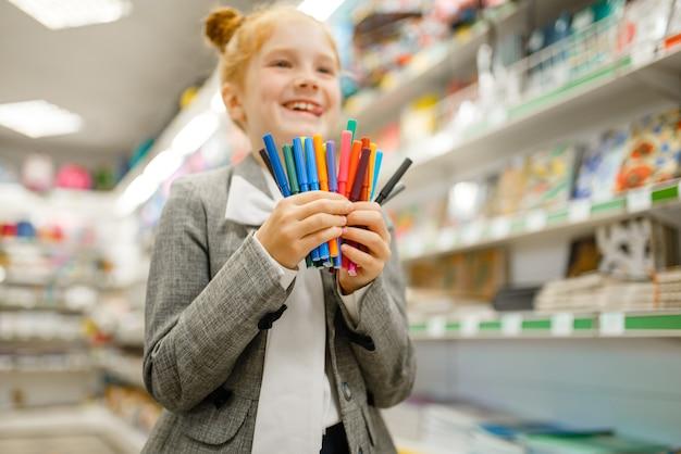 La petite écolière tient des marqueurs colorés, faisant du shopping dans une papeterie