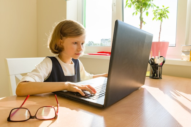 Petite écolière utilise un ordinateur
