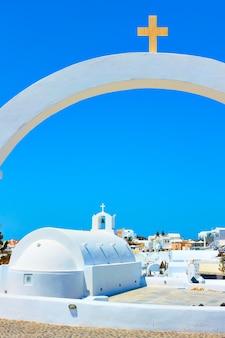 Petite église grecque blanche à travers l'arche avec croix, île de santorin, grèce