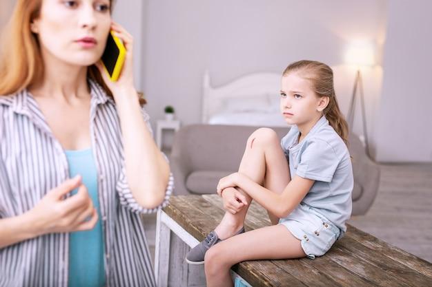 Petite égratignure. triste fille sans joie en regardant sa mère tout en ayant une égratignure sur sa jambe