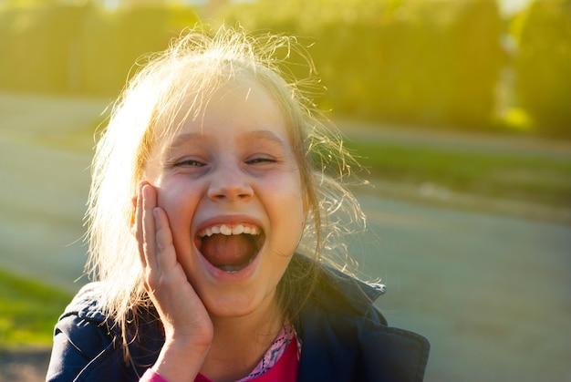 Petite émotion belle fille souriante blonde pose des visages gros plan. journée ensoleillée. fond