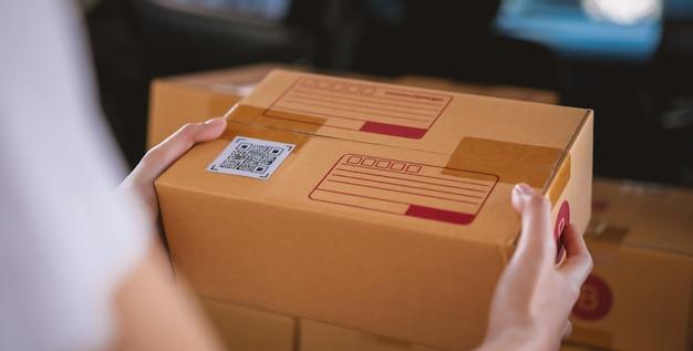 Petite entreprise en démarrage, boîtes d'emballage à la main pour les produits à envoyer aux clients, travaillant au bureau à domicile.
