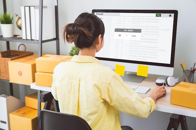 Petite entreprise de démarrage, jeune femme vérifiant le courrier électronique sur l'ordinateur
