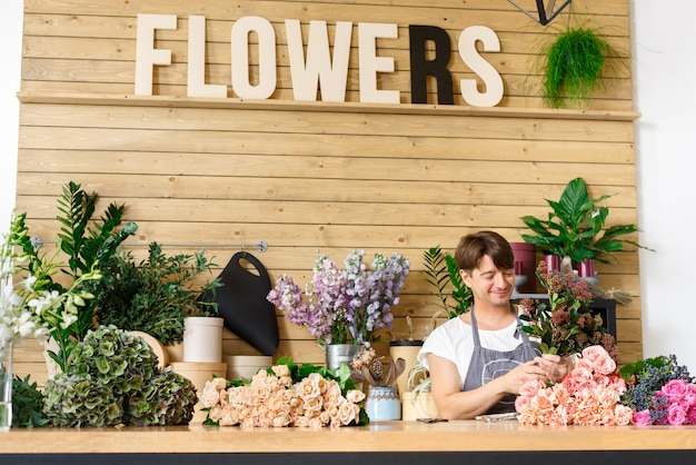 Petite entreprise. fleuriste mâle faisant un bouquet de roses au comptoir de fleuriste. homme assistant ou propriétaire dans un studio de design floral, faisant des décorations et des arrangements. livraison de fleurs, création de commande