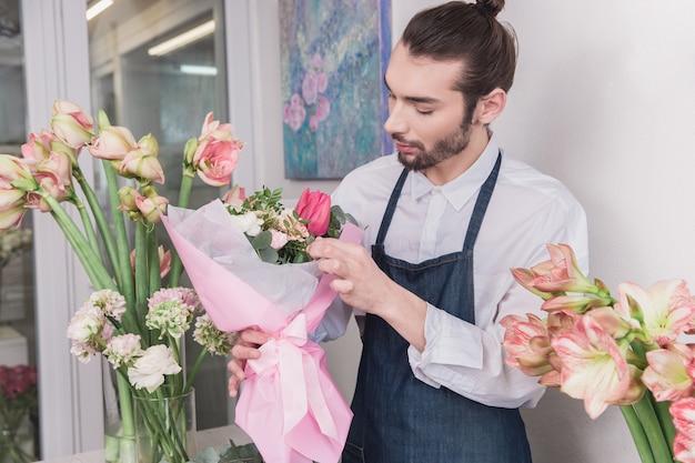 Petite entreprise. fleuriste mâle en magasin de fleurs. faire des décorations et des arrangements