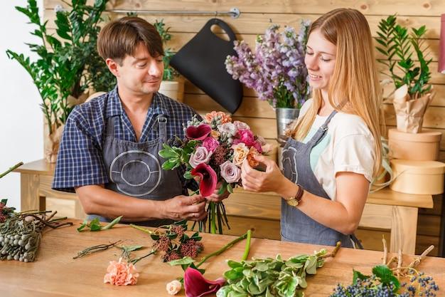 Petite entreprise. fleuristes mâles et femelles faisant un bouquet de roses dans un magasin de fleurs. propriétaire de l'homme et assistante dans un studio de design floral, faisant des décorations et des arrangements. livraison de fleurs, création de commande