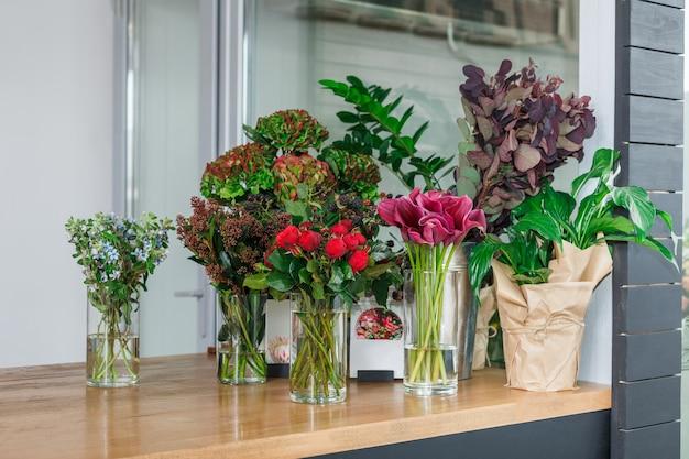Petite entreprise. intérieur de magasin de fleurs moderne. atelier de création florale, vente de décors et arrangements. service de livraison de fleurs et vente de plantes à domicile en pots, vitrine en bois.