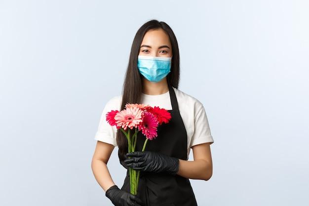 Petite entreprise, pandémie de coronavirus, commandes et concept de magasins. fleuriste asiatique mignonne souriante en masque médical, tenant un bouquet pour le client, vendant des fleurs pendant l'épidémie de covid-19.