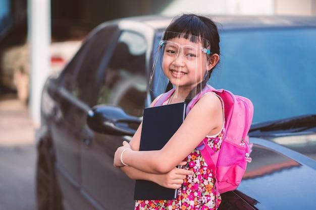 Petite étudiante asiatique portant un écran facial lors de son retour à l'école après la quarantaine de covid-19.