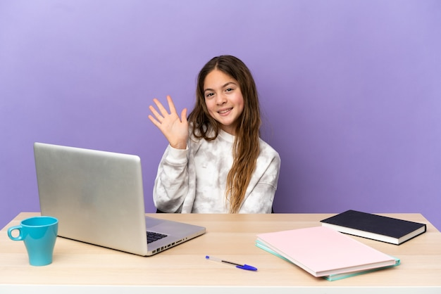 Petite étudiante dans un lieu de travail avec un ordinateur portable isolé sur fond violet saluant avec la main avec une expression heureuse