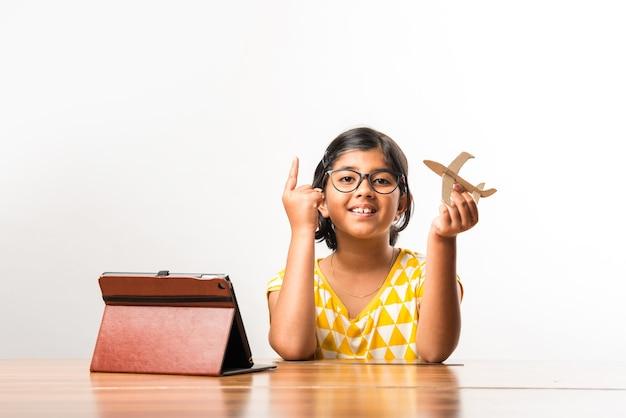 Petite étudiante indienne fabriquant ou mesurant des ailes d'avion en papier ou d'avion, faisant un projet scolaire ou apprenant les sciences avec un didacticiel en ligne