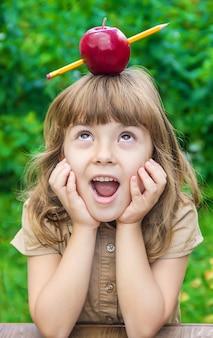 Petite étudiante avec une pomme rouge. mise au point sélective. la nature.