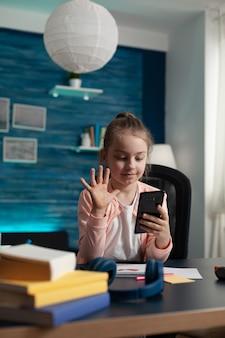 Petite étudiante utilisant l'appel vidéo sur smartphone