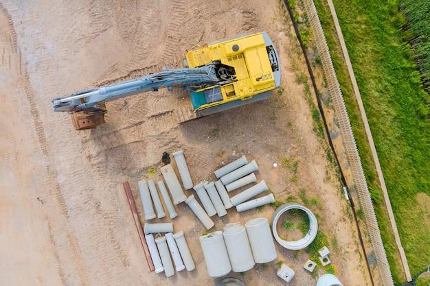 Petite excavatrice au tuyau de drainage en béton empilé dans un immeuble d'appartements sur un chantier de construction