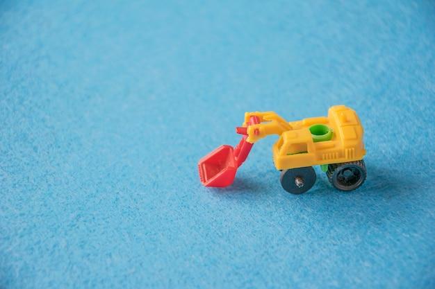 Petite excavatrice de jouet décoratif sur bleu