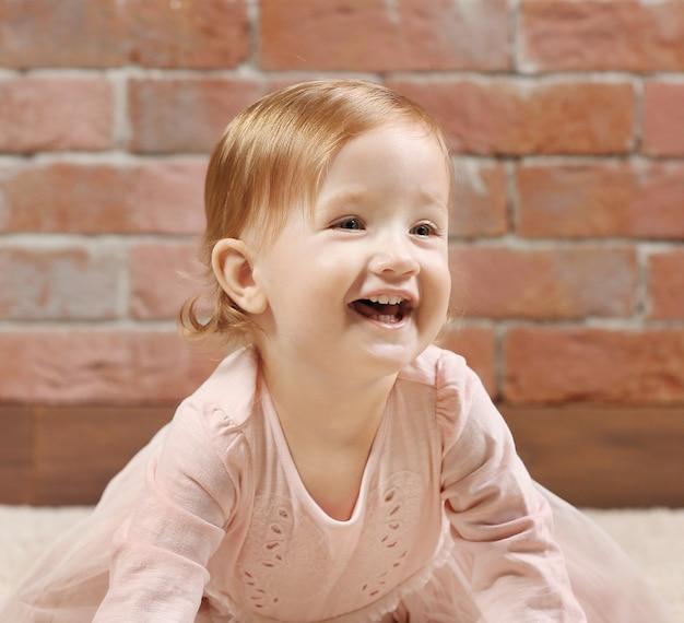Petite fashion-girl en robe rose posant sur un mur de briques