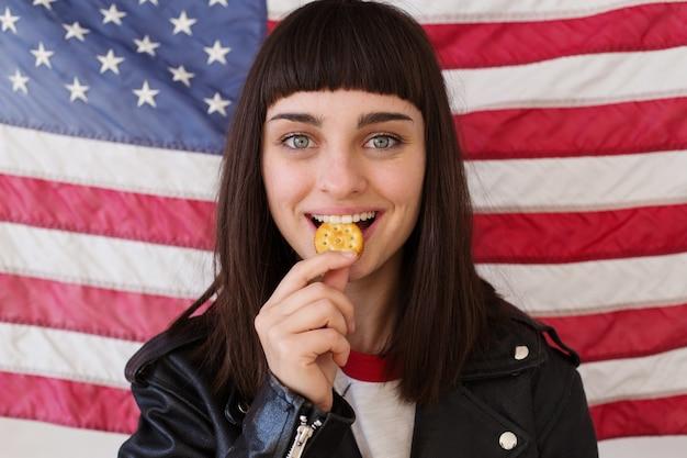 Petite femme ou adolescent en tenue hipster à la mode mange des poses avec biscuit au beurre d'arachide croustillant, snack américain traditionnel typique avec le drapeau des états-unis