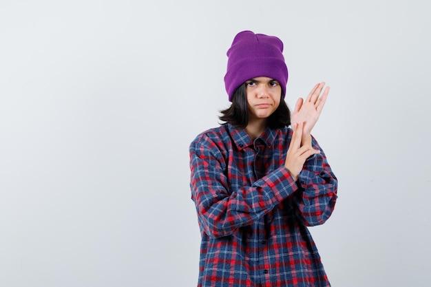 Petite femme bonnet frottant les paumes à la grave