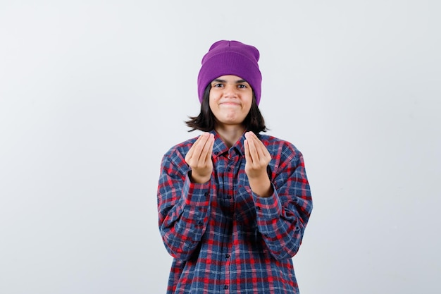 Petite femme en chemise à carreaux et bonnet montrant un geste italien et l'air ravi