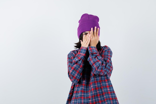 Petite femme en chemise à carreaux et bonnet regardant à travers et les doigts à la peur