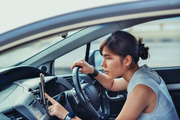 Petite femme heureuse détendue en vacances de voyage. s'asseoir sur la voiture et chercher un itinéraire. concept de mode de vie et de personnes.