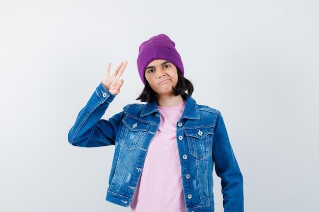 Petite femme montrant un geste ok dans une veste en jean t-shirt à l'air confiant