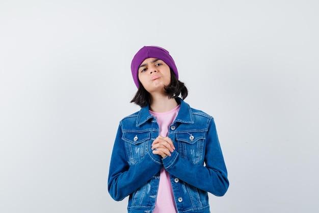 Petite femme montrant les mains jointes dans un geste implorant à l'espoir