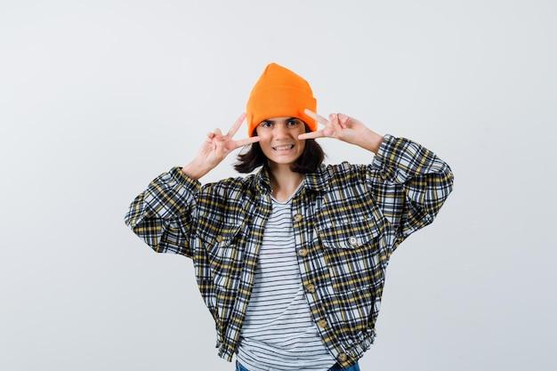 Petite femme en t-shirt et veste et bonnet montrant le signe de la victoire et à la félicité