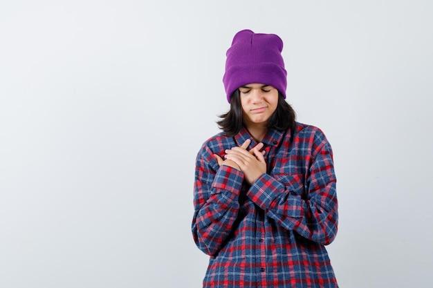 Petite femme tenant la main sur le bonnet de poitrine à la recherche d'espoir