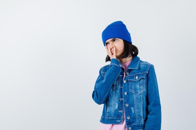 Petite femme tenant la main sur la joue en t-shirt et veste en jean à la nostalgie