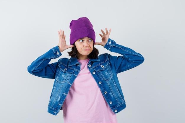 Petite femme en veste en jean t-shirt tenant les mains au-dessus de la tête comme des oreilles à la recherche de drôles