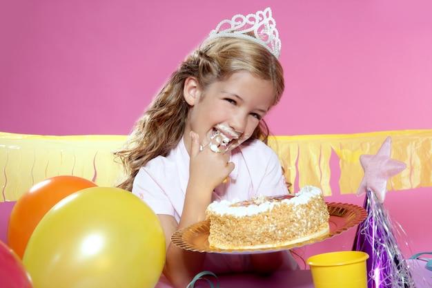 Petite fête d'anniversaire blonde gâteau girleating avec les mains