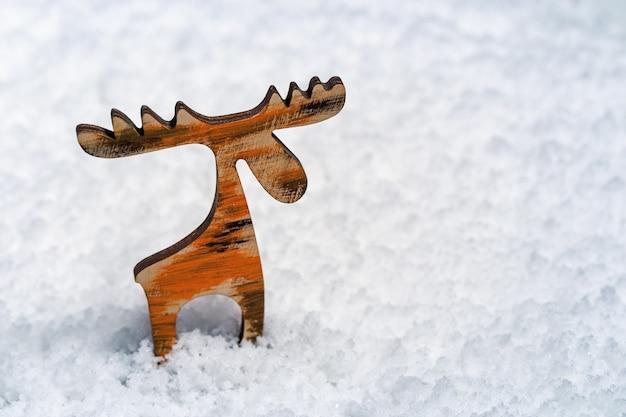 Petite figure en bois de cerf sur la neige avec un espace vide concept pour le nouvel an ou joyeux noël