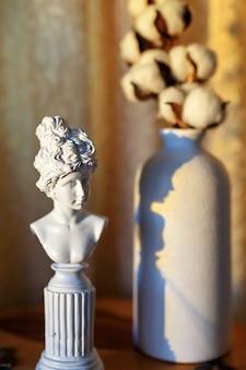Une petite figure féminine antique en plâtre, son ombre et un vase avec un cotonnier. dans le style du monumentalisme.