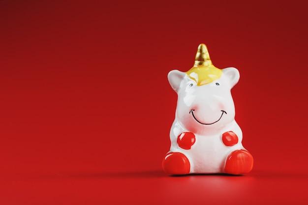 Petite figurine de licorne sur fond rouge.