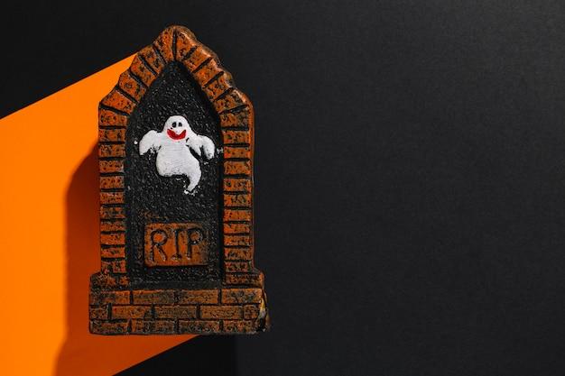 Petite figurine de pierre tombale avec inscription rip et fantôme sur papier orange