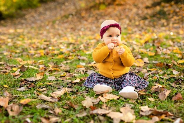 Une petite fille de 1 an vêtue d'une chemise jaune et d'un chapeau blanc est assise dans une poussette grise dans le parc.