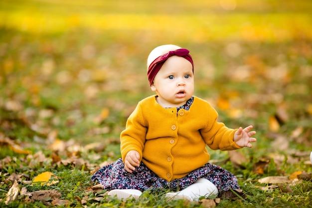 Une petite fille de 1 an vêtue d'une chemise jaune
