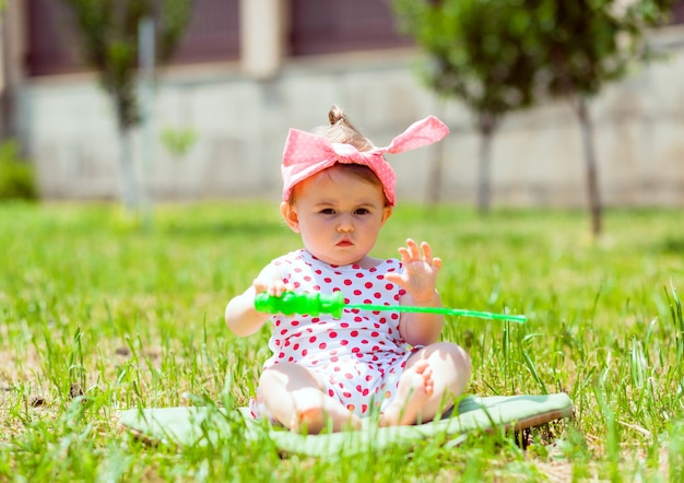 Petite fille de 11 mois est assise dans le parc sur l'herbe. petite fille dans une veste à pois est assise sur l'herbe et joue avec des bulles de savon.