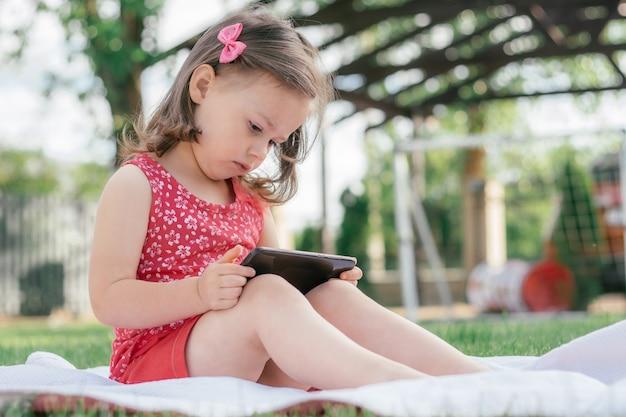 Une petite fille de 3 à 4 ans en vêtements rouges est assise sur une couverture sur l'herbe verte et se penche sur le téléphone portable. enfants, utilisant des gadgets