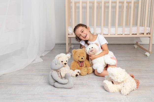 Petite fille de 5 à 6 ans jouant dans la chambre des enfants avec des ours en peluche