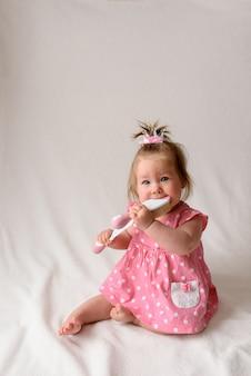 Petite fille de 6 mois avec un peigne à la main sur un mur blanc