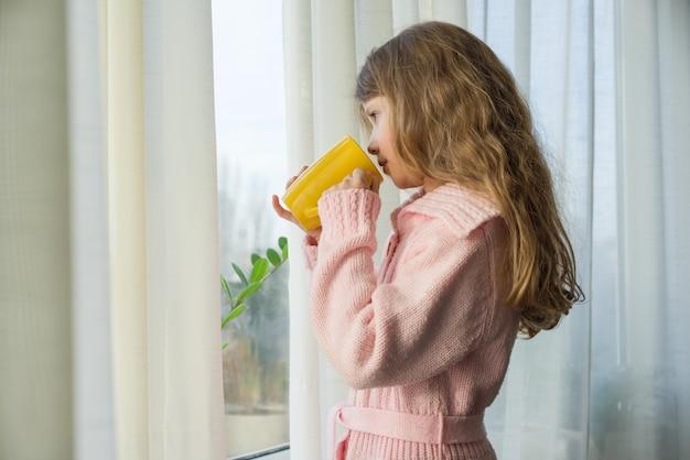 Petite fille de 7 ans blonde avec une tasse de thé
