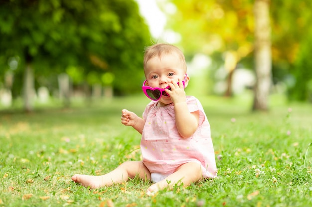 Petite fille de 7 mois assise sur l'herbe verte dans un body rose et des lunettes lumineuses, marchant au grand air