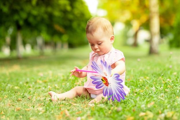 Petite fille de 7 mois jouant sur une pelouse verte dans un body rose, marchant au grand air, développement précoce des enfants jusqu'à un an