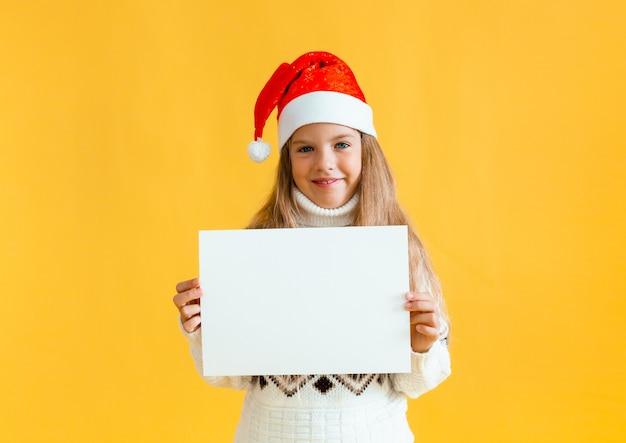 Une petite fille de 8 ans aux cheveux blonds coiffée d'un chapeau de père noël tient une feuille de papier blanc sur fond jaune.