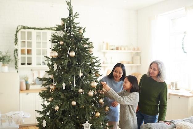 Petite fille accrocher des boules de noël sur l'arbre de noël avec sa sœur aînée et sa mère dans la chambre